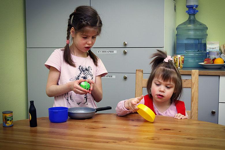 Ангелина внимательно разглядывает игрушечную посуду – в интернате таких чудес не было